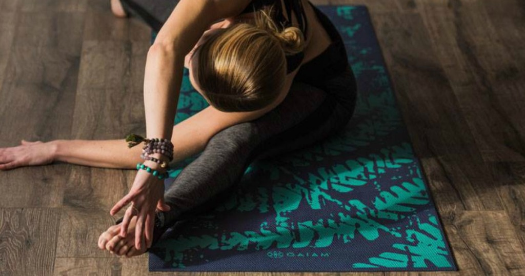 Woman in yoga post on navy blue and green yoga mat on hardwood flooring