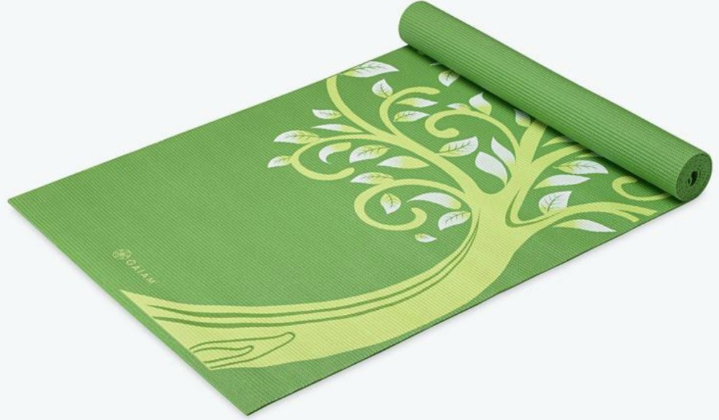 Green yoga mat with tree print, partially unrolled