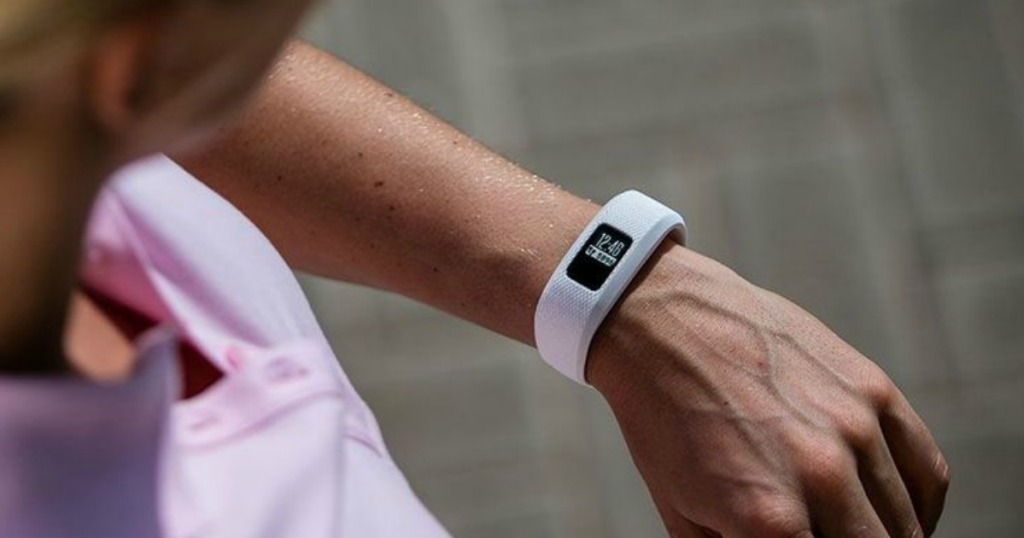 woman wearing a white fitness tracker on her wrist