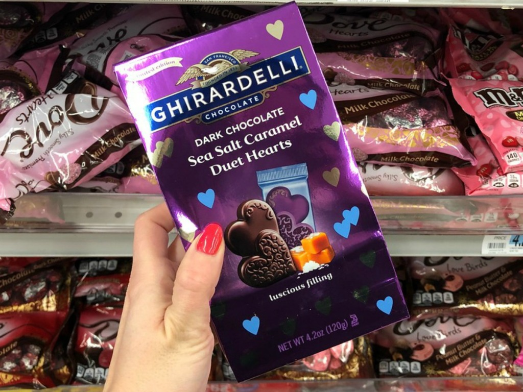 Hand holding a purple bag of gourmet chocolates near in-store display of Valentine's Day candy clearance