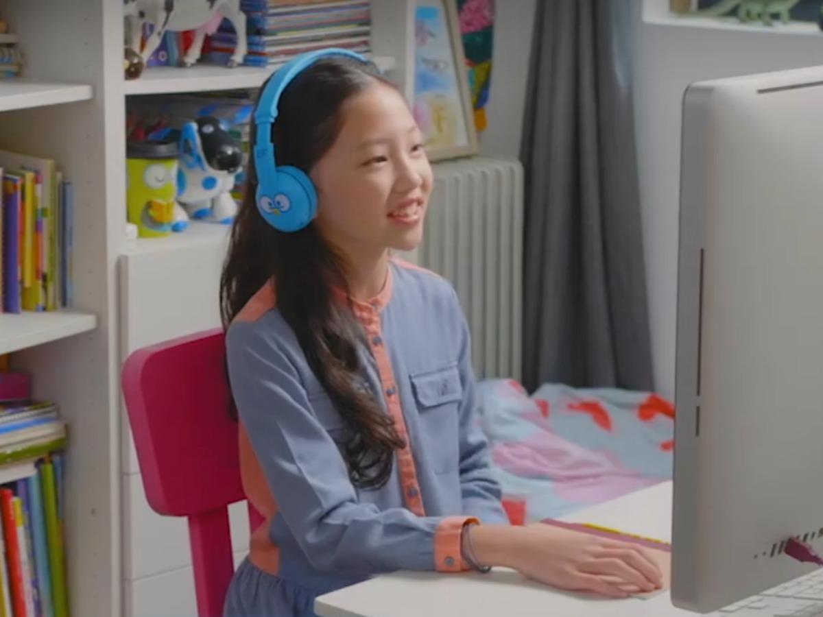 girl wearing headphones and working on desktop computer