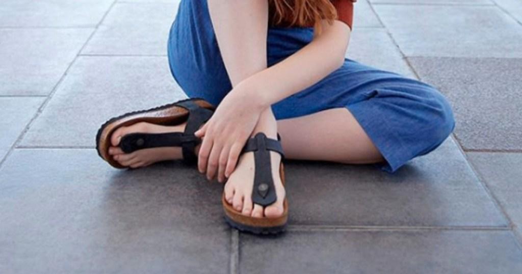 woman's legs wearing gizeh Birkenstocks sitting cross legged