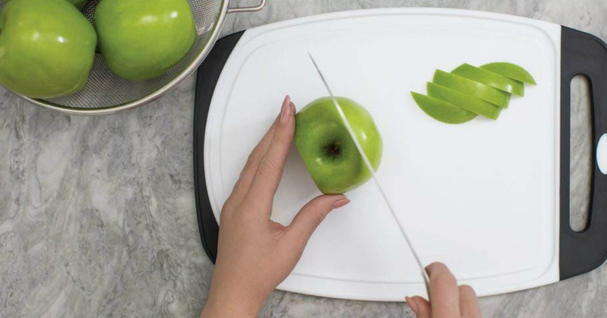 person cutting apples on a cutting board
