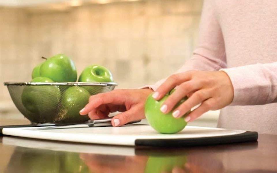 woman cutting an apple on a cutting board