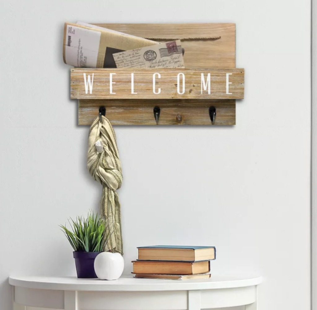 Gray Wood Welcome Mail Station hanging above a console table with books and a plant on it