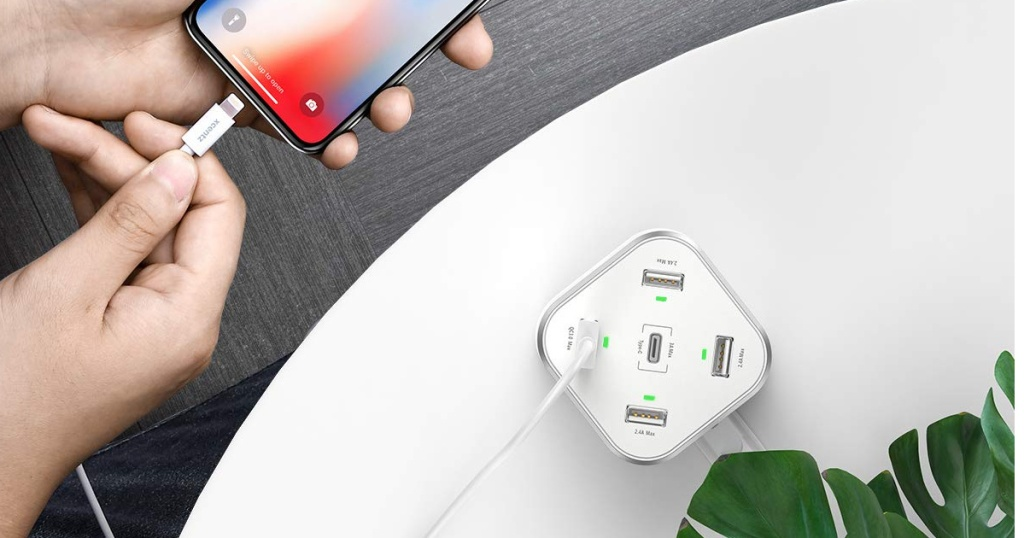 grey Xcentz USB Charger 5-Port Charging Block with hand plugging in iphone
