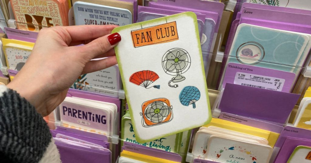woman hand holding hallmark card with fans on it and says fan club