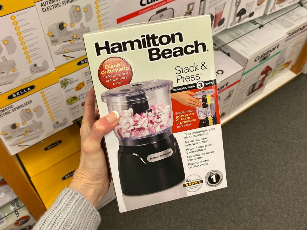 Hand holding box with mini food processor inside near in-store display