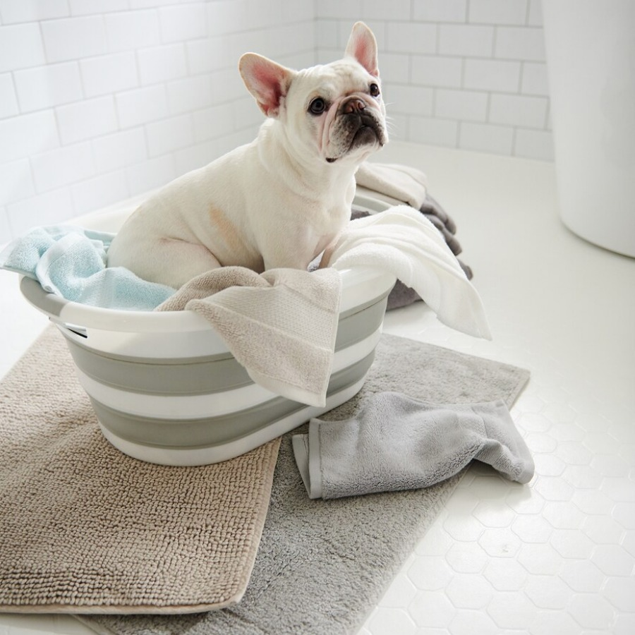 Happitat Quick Dry Bath Rugs shown in gray and Tan with dog in laundry basket on top of them