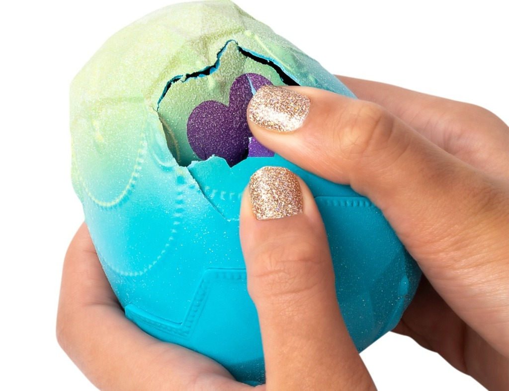 girl with golden glittery fingernails breaking into a Hatchimals Pixies Egg