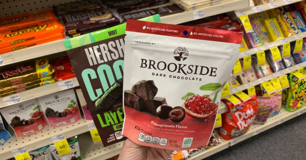 Hand holding chocolate candy in front of shelf