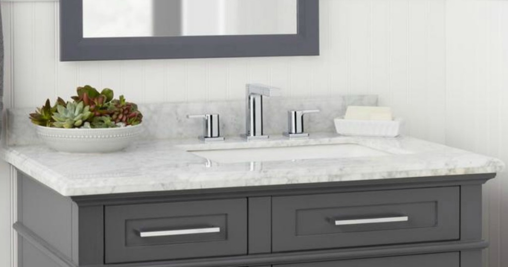 a bathroo setup with chrome faucet on vanity with mirror above