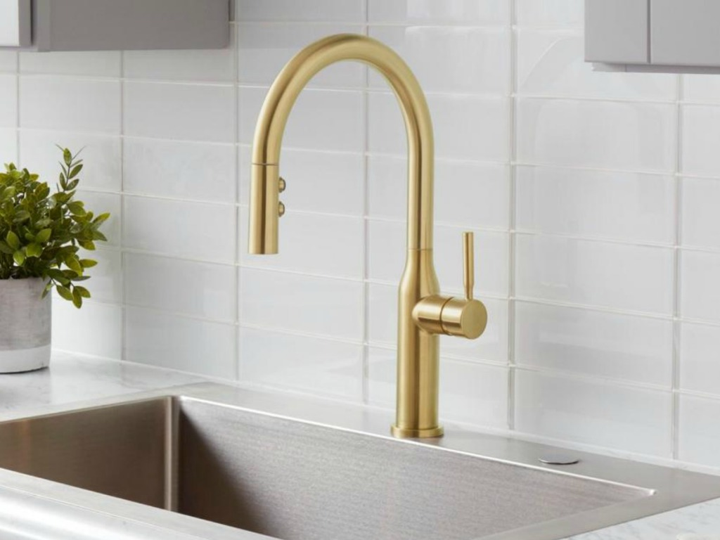 Large golden kitchen sink faucet on a sink near a subway tile backsplash and a small potted plant