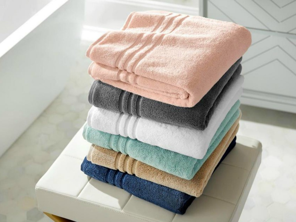 Large stack of folded bath towels in bathroom - in a variety of colors