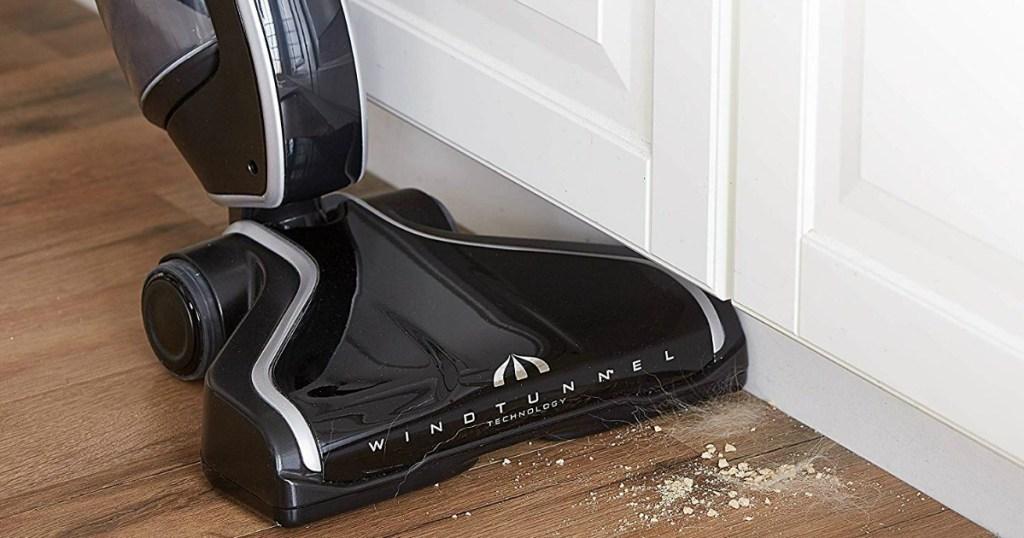 black vacuum cleaning up dirt off floor