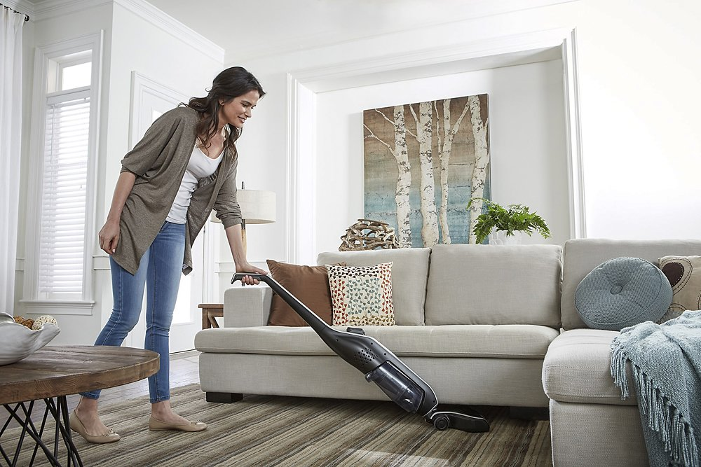 woman vacuuming carpet in living room by couch