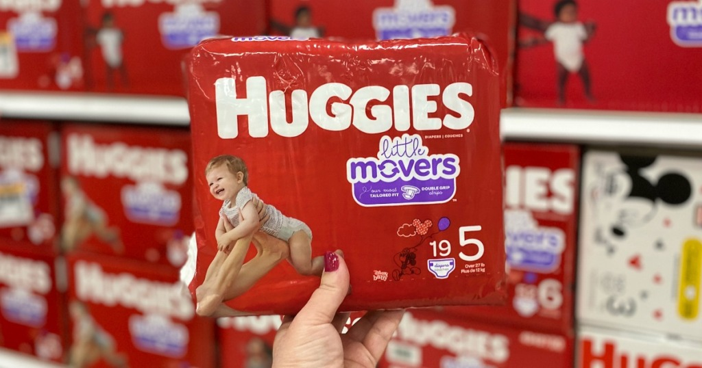 Hand holding up Huggies Diapers