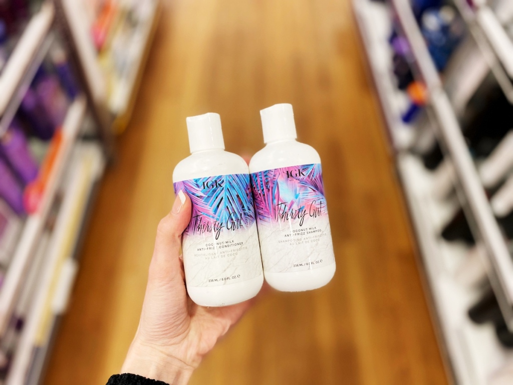 woman hand holding IGK Thirty Girls Shampoo and Conditioners