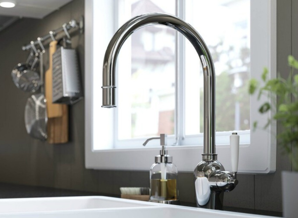 Large stainless steel kitchen faucet installed in kitchen sink
