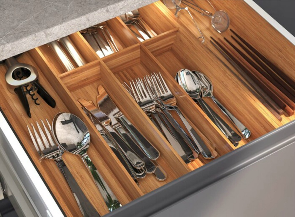 Large wooden flatware organizer filled with a matching set of forks, spoons, and knives