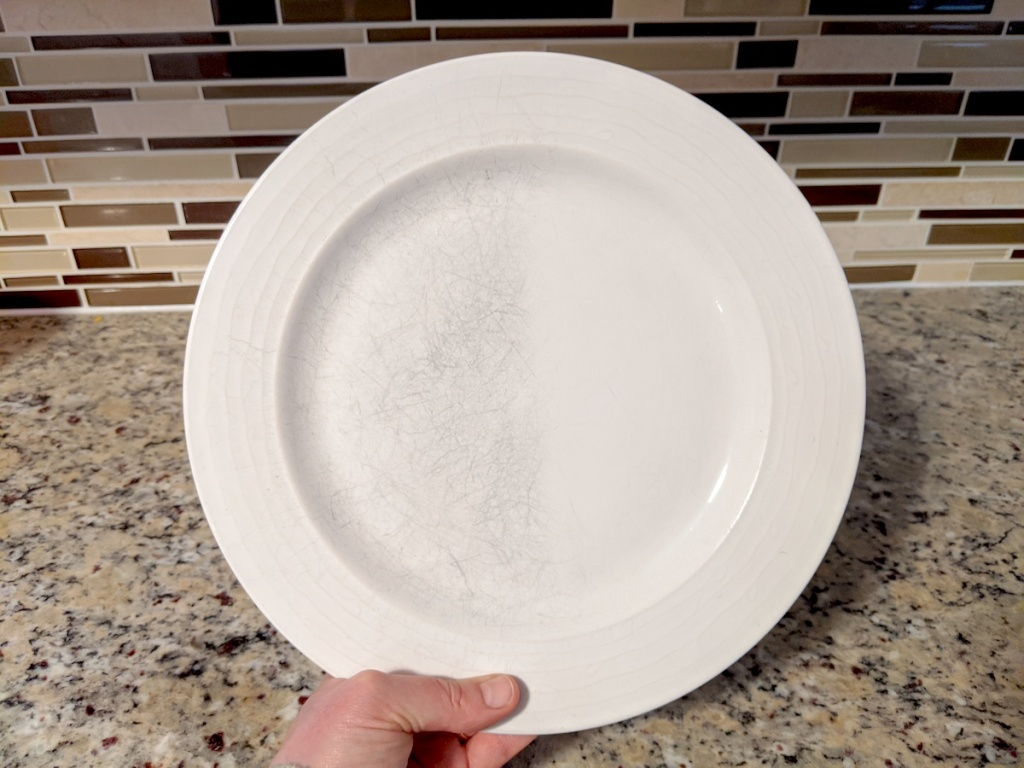 hand holding a white plate with clean side and scratched side