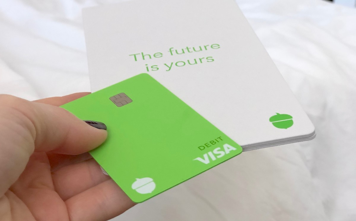 hand holding a green visa card with white pamphlet