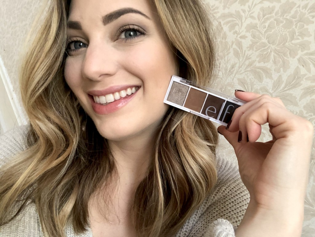 woman smiling holding small eyeshadow pallet with four colors