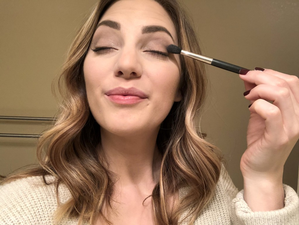 woman putting on makeup with brush