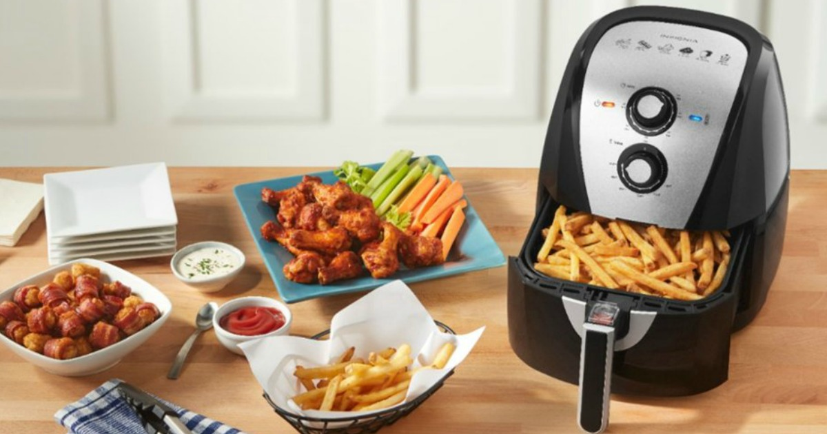black and silver air fryer on a counter surrounded by various fried foods