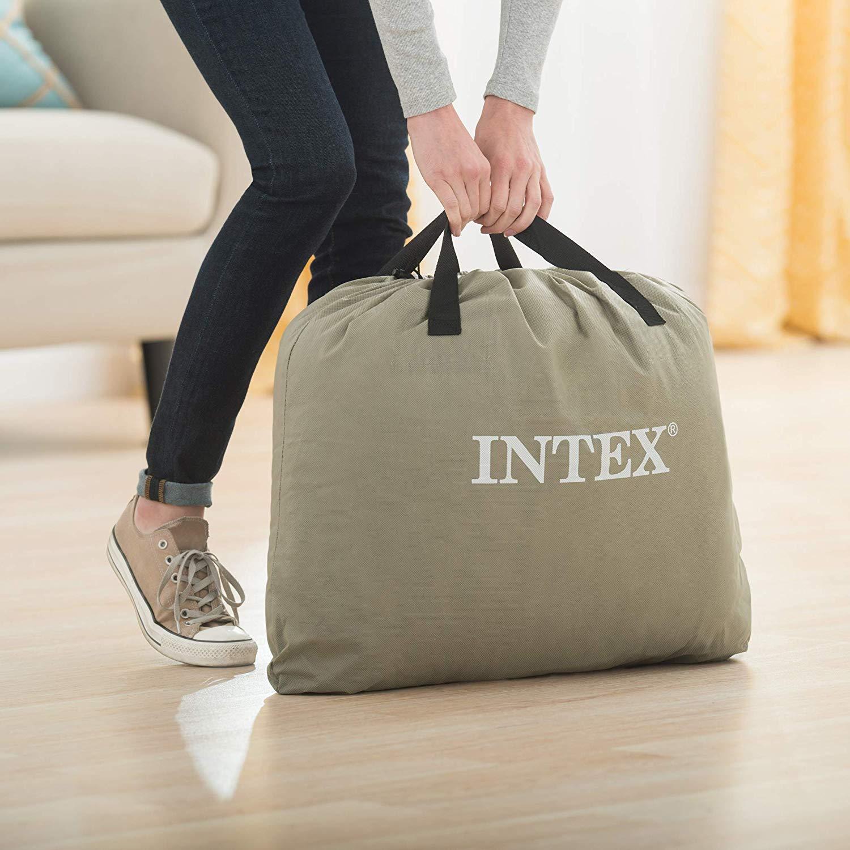 Woman lifting Intex air mattress stored in duffel bag