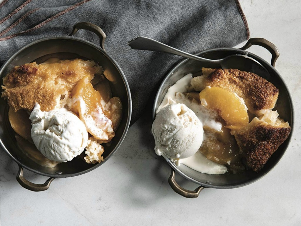 Peach cobbler dish in cast iron skillet bowls with gray towel