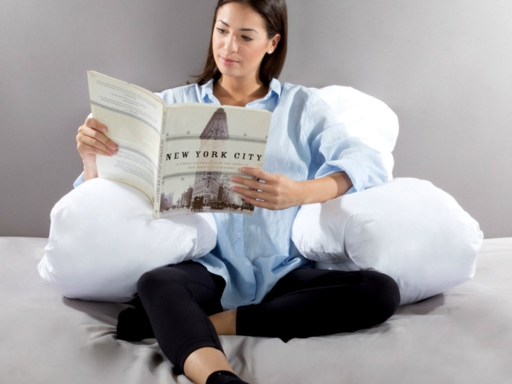 Woman sitting in bed reading with a jumbo white body pillow