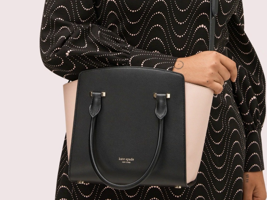 Woman holding a black and pink handbag while wearing a black dress with silver wavy lines