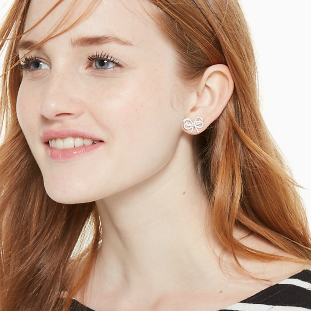 woman wearing sparkly bow earrings