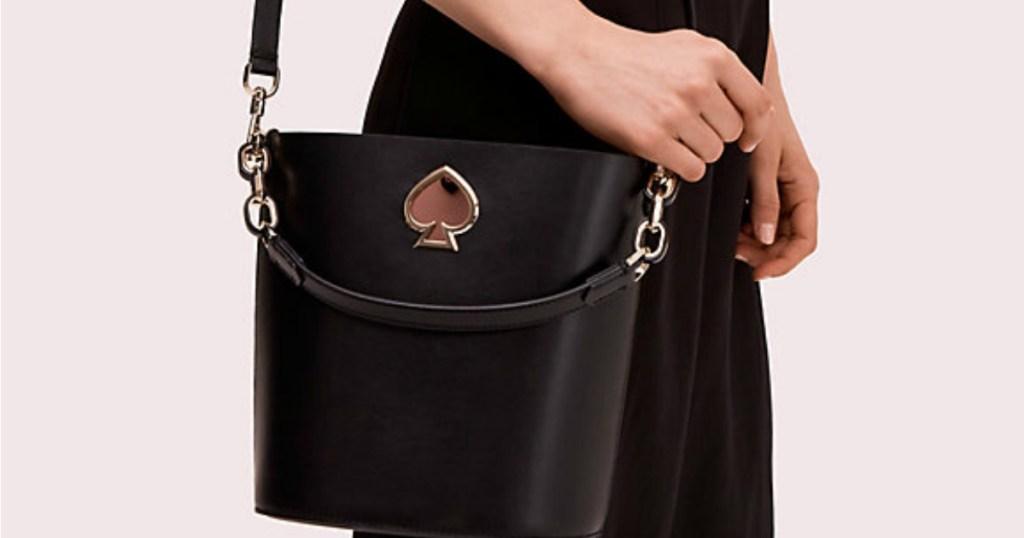 woman holding Kate Spade Bucket Bag