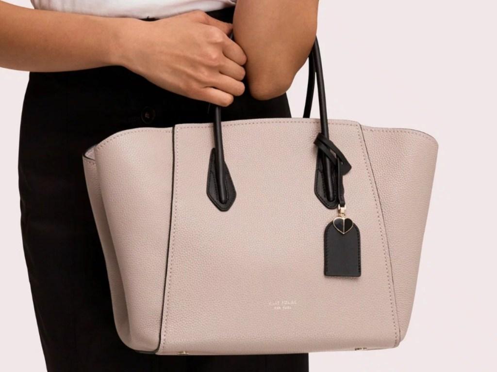 Woman holding a light pink handbag with dark straps