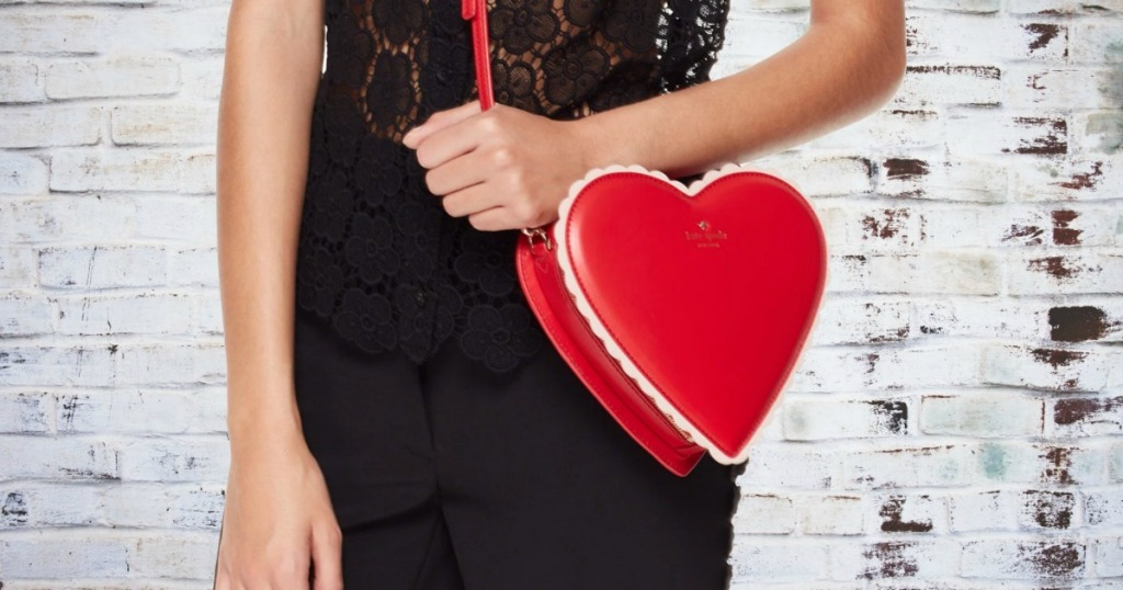 Woman in front of a brick wall wearing a red heart-shaped purse