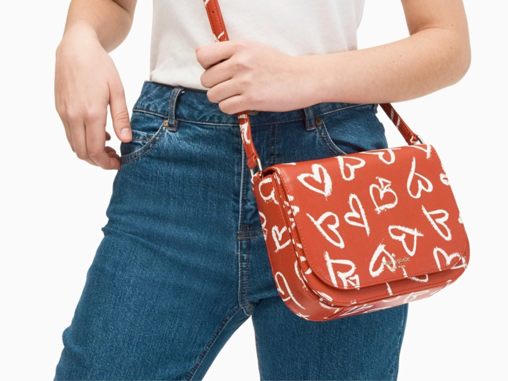 Woman holding red bag with white heart design