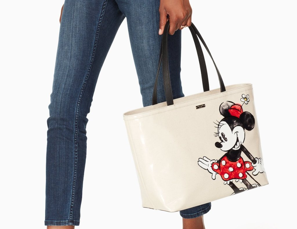 woman carrying a Kate Spade tote with Minnie Mouse on it