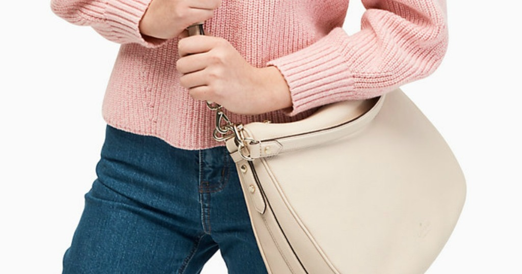 woman in pink sweater holding a beige purse