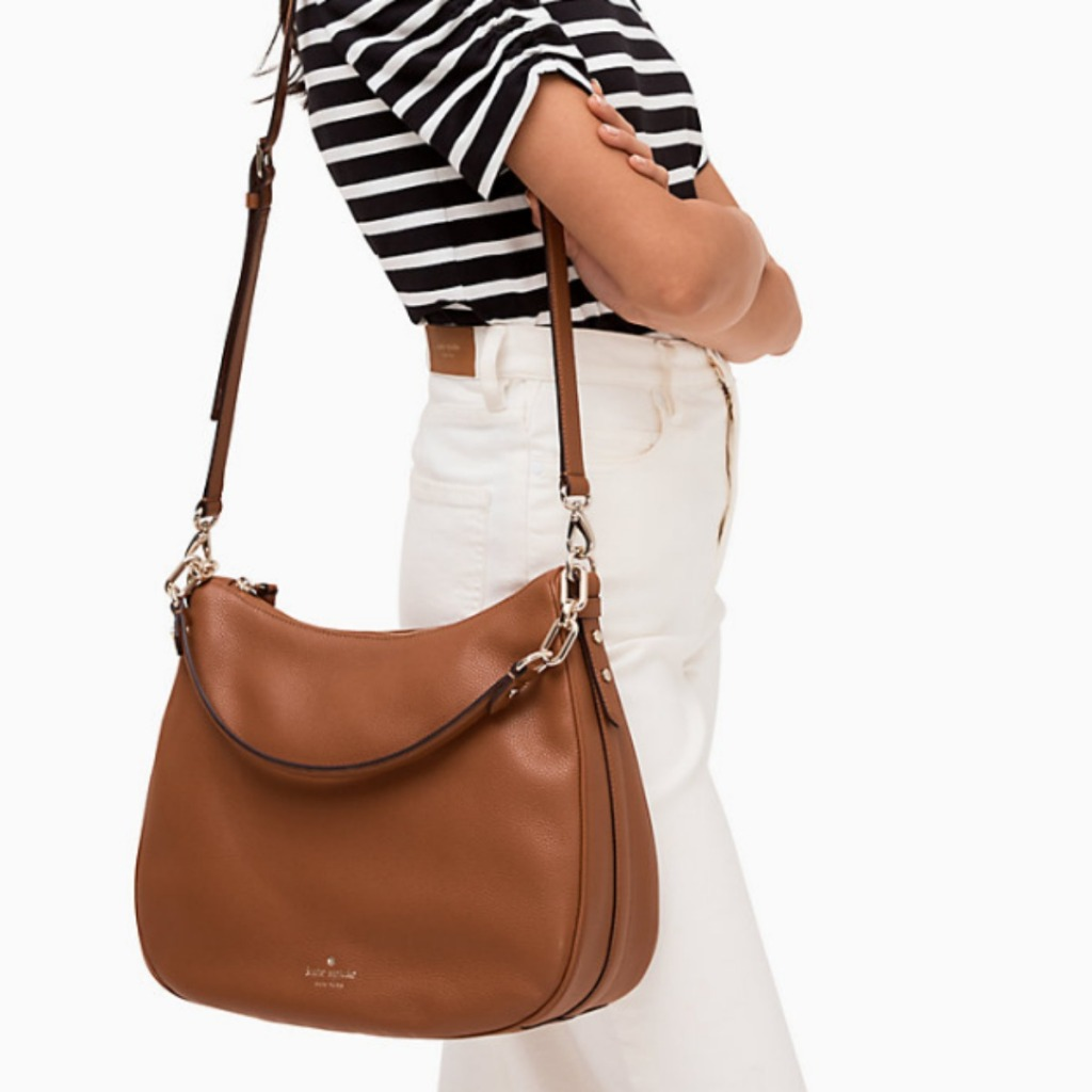woman holding brown purse