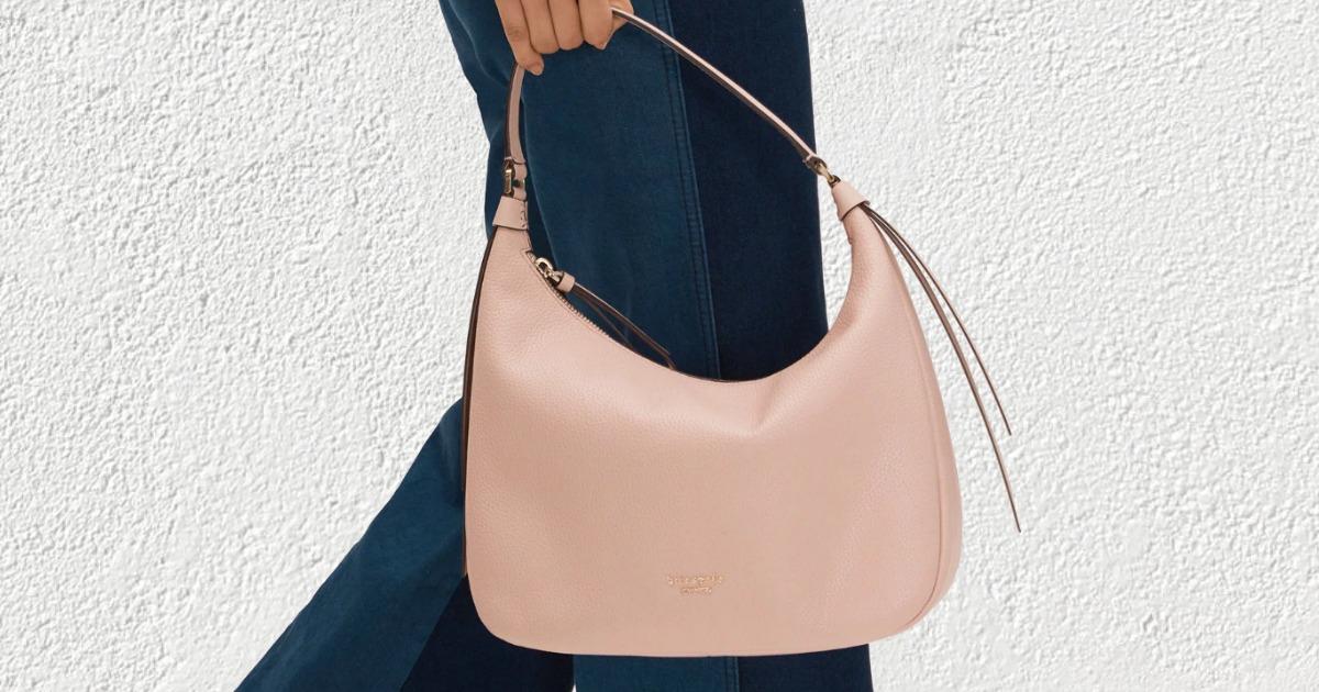 Woman holding a pink handbag while wearing denim jeans