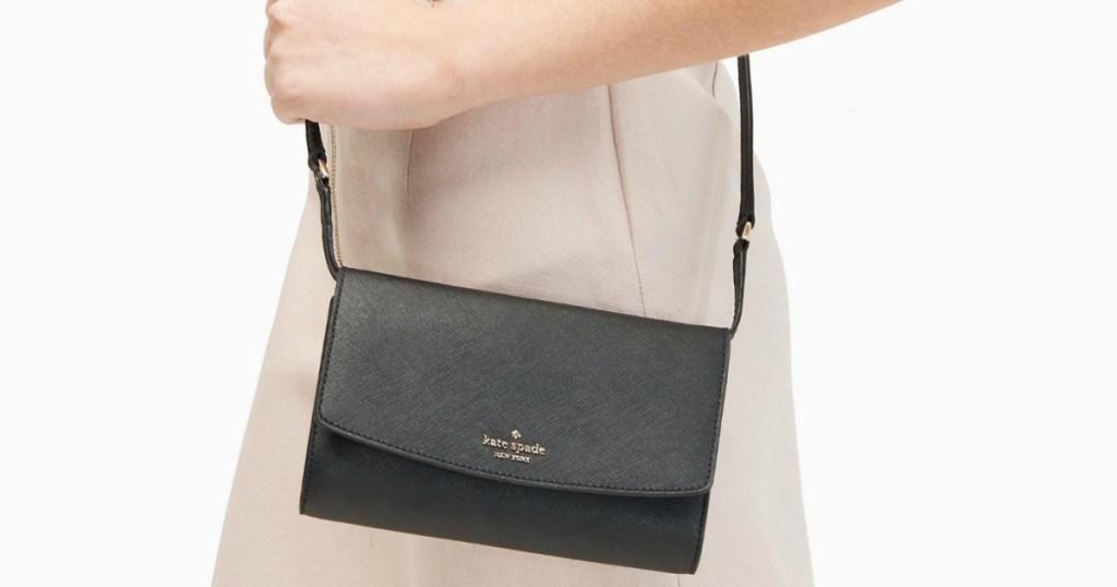 woman holding a black Kate Spade purse