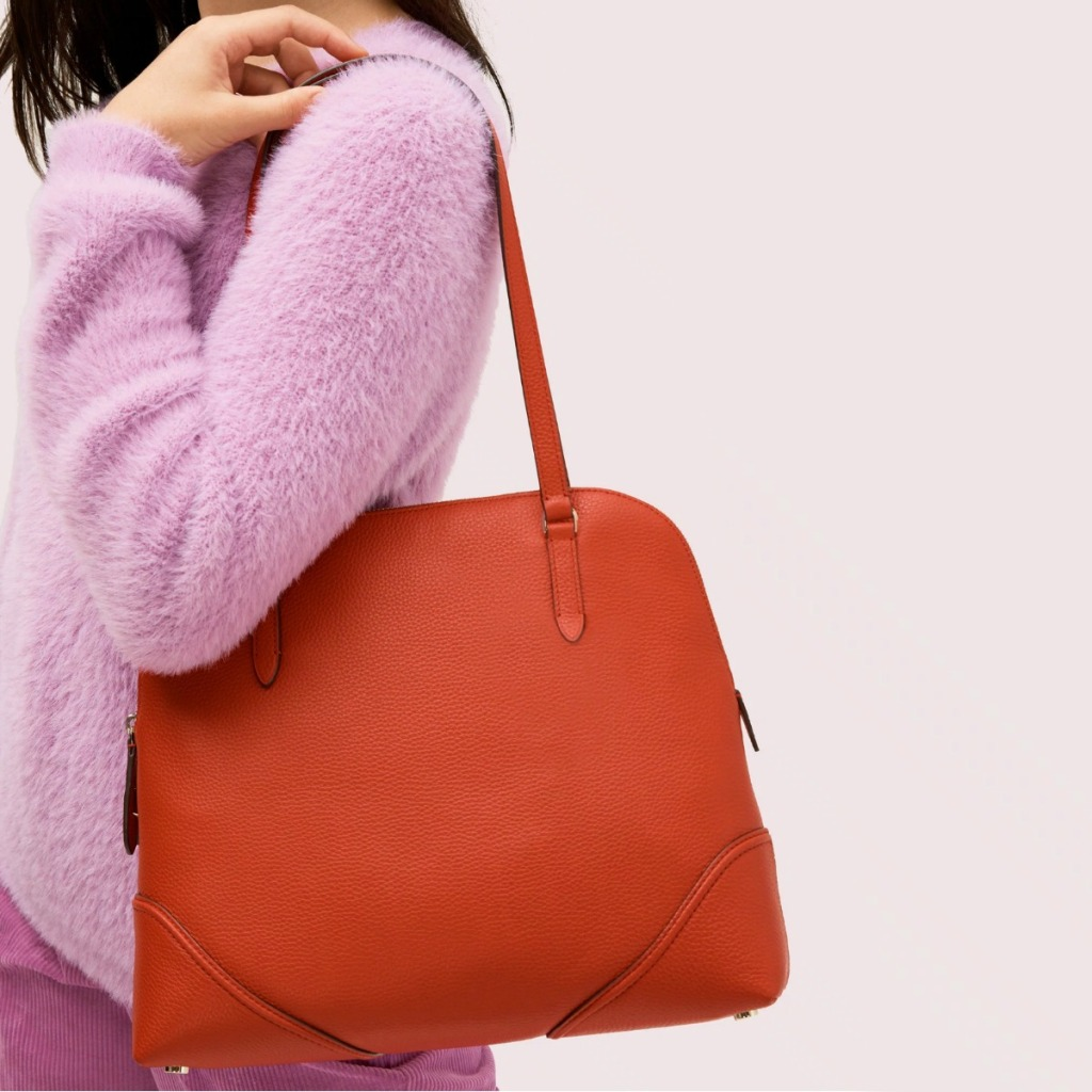 Woman wearing a light pink sweater and a red shoulder bag