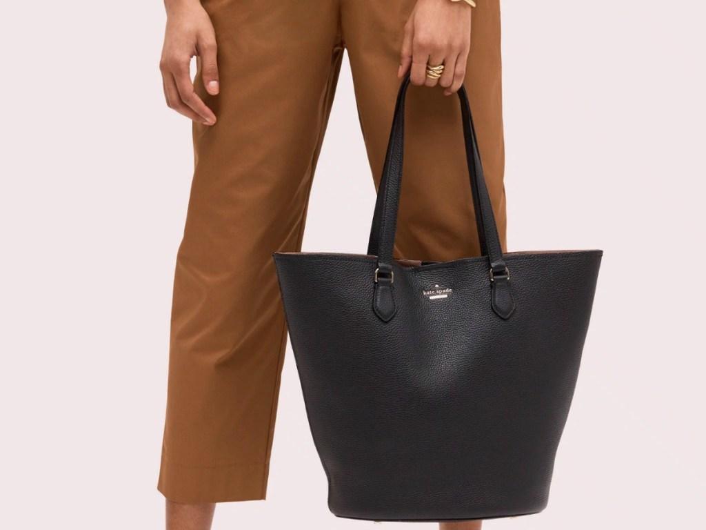 Woman wearing brown pants, holding a black tote bag