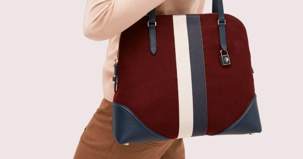 Woman wearing a large maroon purse with white and navy stripe