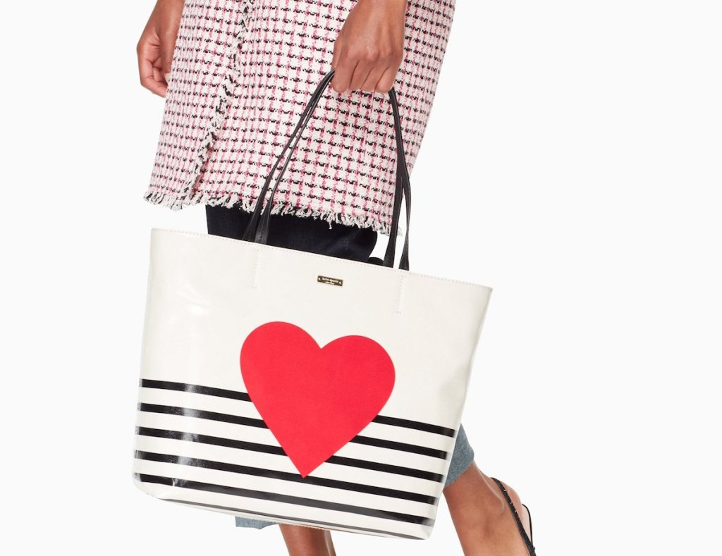 woman carrying a Kate Spade tote with a heart and stripes on it