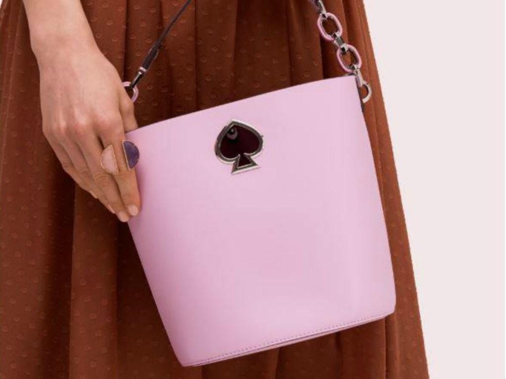 woman carrying Kate Spade Bucket Bag in pink