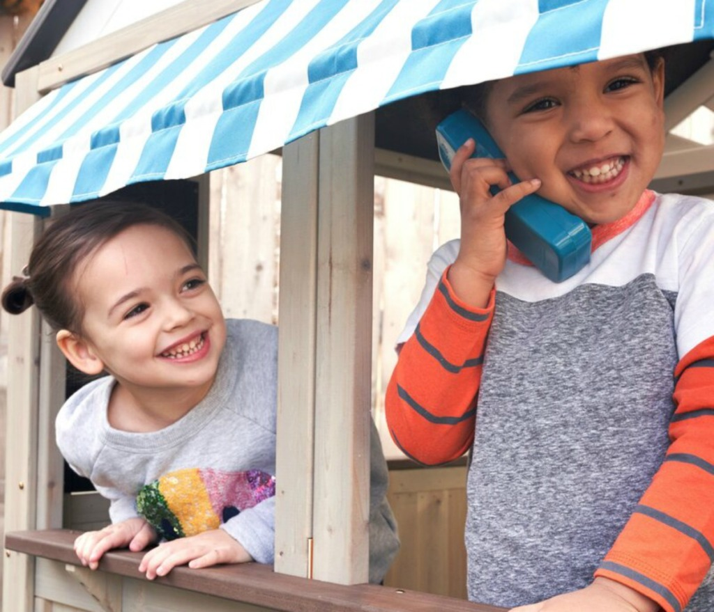 kids playing in a playhouse with a play phone