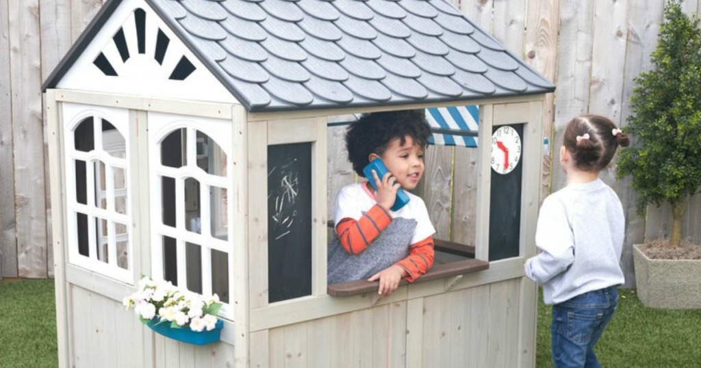 kids playing in a Kidkraft Wood Hillcrest Outdoor Playhouse